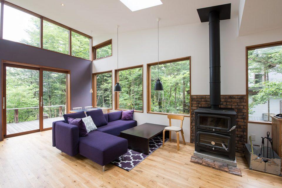 紫のソファと薪ストーブが出迎えます