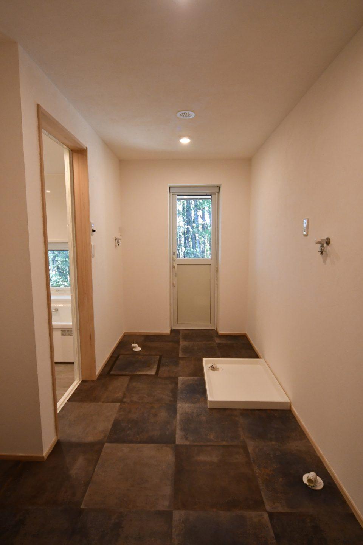 洗濯機が2台、犬用トイレとしての洗濯機パンが置かれている。 床はPタイル。
