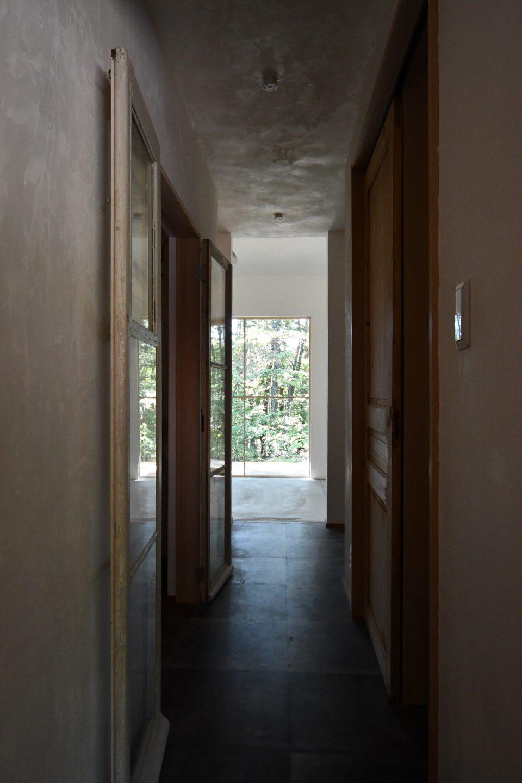 個人的にこの家で一番好きなカメラアングル。 水廻りてとつながる廊下から南を向いている。 しっくい壁に反射する太陽光が、とても美しいと感じる。
