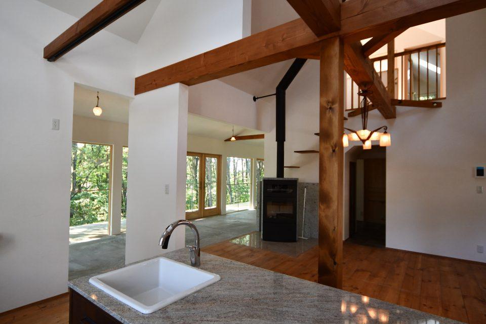 キッチンよりダイニング方向をみる。 小屋裏の2階とも空間的につながっており、薪ストーブが家の中心に据えられている。