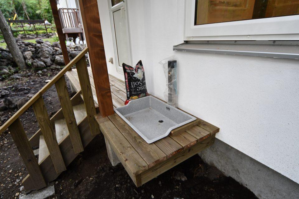 デッキ床と地面の高低差を活かし、市販のガーデンパンをデッキ床に埋め込み、大型犬の体を洗う場所となっている。