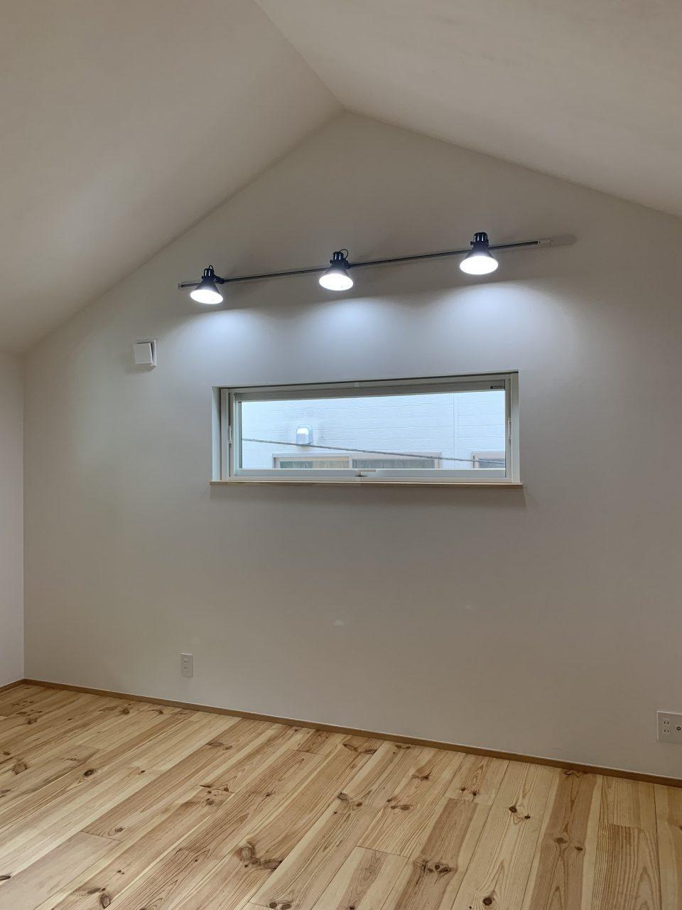 ホームベース型の壁を持つ2階の個室。 意外に困るのが照明の位置。この家では壁面にライティングレールで対応。 壁面や勾配天井面を照らすことで間接照明風に。