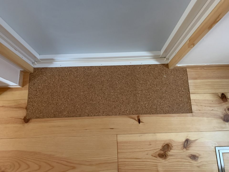 洗面脱衣室の床はかなり迷った末に、ボルドーパインのフローリングを。 浴室入口は傷みやすいので、コルクタイルを部分的に貼っている。