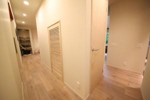 玄関から廊下へのアプローチ。いわゆる階段下スペースにドア